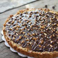 Close up shot of chocolate caramel pretzel tart on a wooden surface.