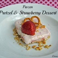 Close up shot of frozen pretzel and strawberry dessert slice garnished with a strawberry and pretzel on a white plate.