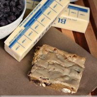 Close up shot of a sweet and salty blondie with chocolate chips and butter sticks in the background.