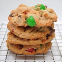 Side view of four caramel corn pretzel cookies stacked on a metal drying rack.