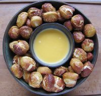 Overhead shot of pretzel bites in a ring around a bowl of cheese sauce.