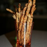 Side shot of gluten free pretzel sticks in a red clear glass.
