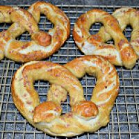 Overhead shot of soft pretzels on a metal drying rack with a black background.