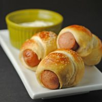 Side view of three mini pretzel dogs on a white plate with a side of horseradish dipping sauce in a green ceramic cup.