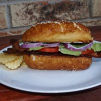 Side view of sandwich with a pretzel bun with a side of potato chips on a white plate with a brick background.