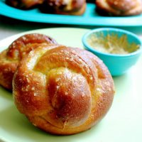 Side view of two pretzel Challah rolls on a green plate with a side of dipping sauce in a blue bowl.