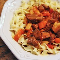 A close up photo of slow cooker Hungarian goulash and noodles in a bowl.