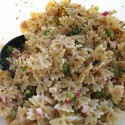 A close up photo of tomato herb pasta salad.