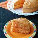 A slice of orange poke cake on an orange plate.