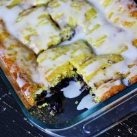 A close up photo of a pan of glazed lemon blueberry cake with a piece missing.