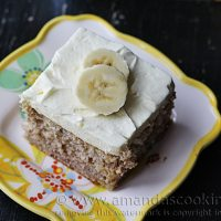 A photo of a square of easy banana cake with banana whipped cream frosting resting on a plate.