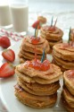 Several stacks of pancakes all topped with strawberries.