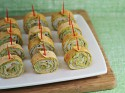 Several wrap bites stabbed with toothpicks on a white appetizer tray.