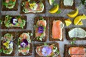 Overhead view of many smoked salmons on a serving tray with various toppings.