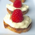 A close up of a row of raspberry topped pastries.